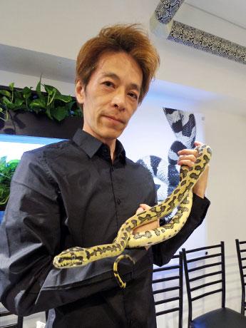 カーペットニシキヘビの「ジャガー」を抱く金子ヒサミツ社長