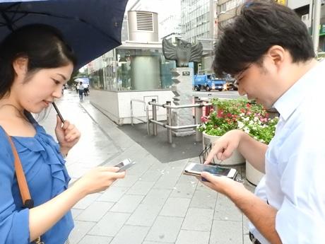 小雨がぱらつく中で、ミッション遂行に向けてポータルを巡る山田さん(左)、水野さん(右)。明治通り・ビッグカメラ前の「ホープくん」を見つけ早速ハックする2人。