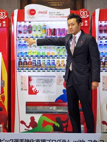 設置するオリジナルラッピングの自販機でコカ・コーラを購入した競泳・北島康介選手