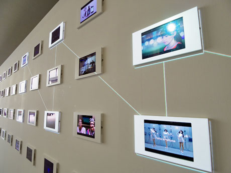 iPad120台で過去の取り組みを紹介する場内。白い線の映像で同様のプロジェクトをつないでいる