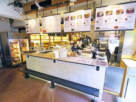 サラダを盛る工程が見られるオープンキッチンが特徴の店内