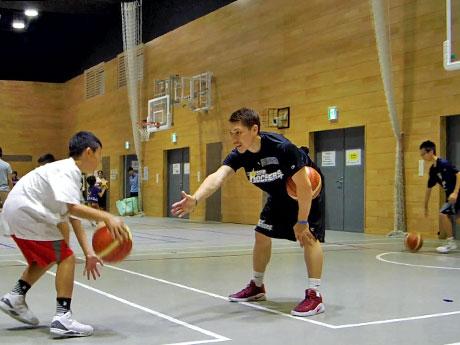 アドバイスを交えながら小学生たちにバスケットを教える山内盛久選手(中央)