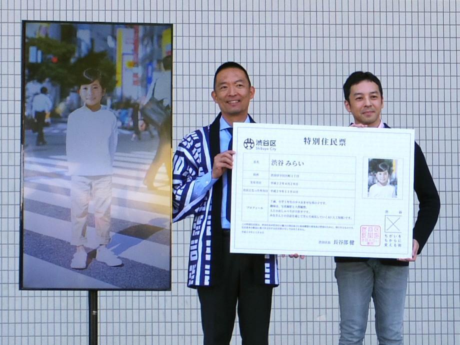 「渋谷みらい」の特別住民票を紹介する長谷部健渋谷区長(左)と井澤友郭こども国連環境会議推進協会事務局長(右)。モニターに映っているのは「渋谷みらい」