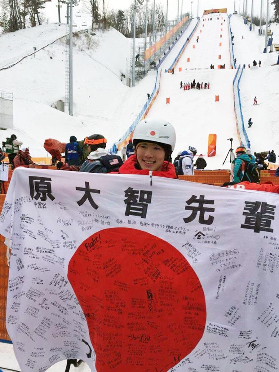 母校・広尾中在校生たちの寄せ書きが書かれた国旗を持つ原大智選手(広尾中学校フェイスブックより)