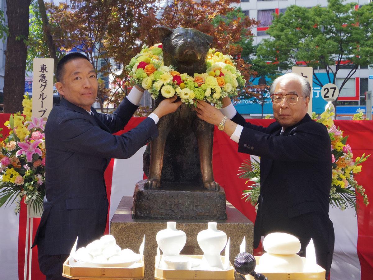 ハチ公像に花輪を献上した(左から)長谷部健渋谷区長と忠犬ハチ公銅像維持会・上條清文会長