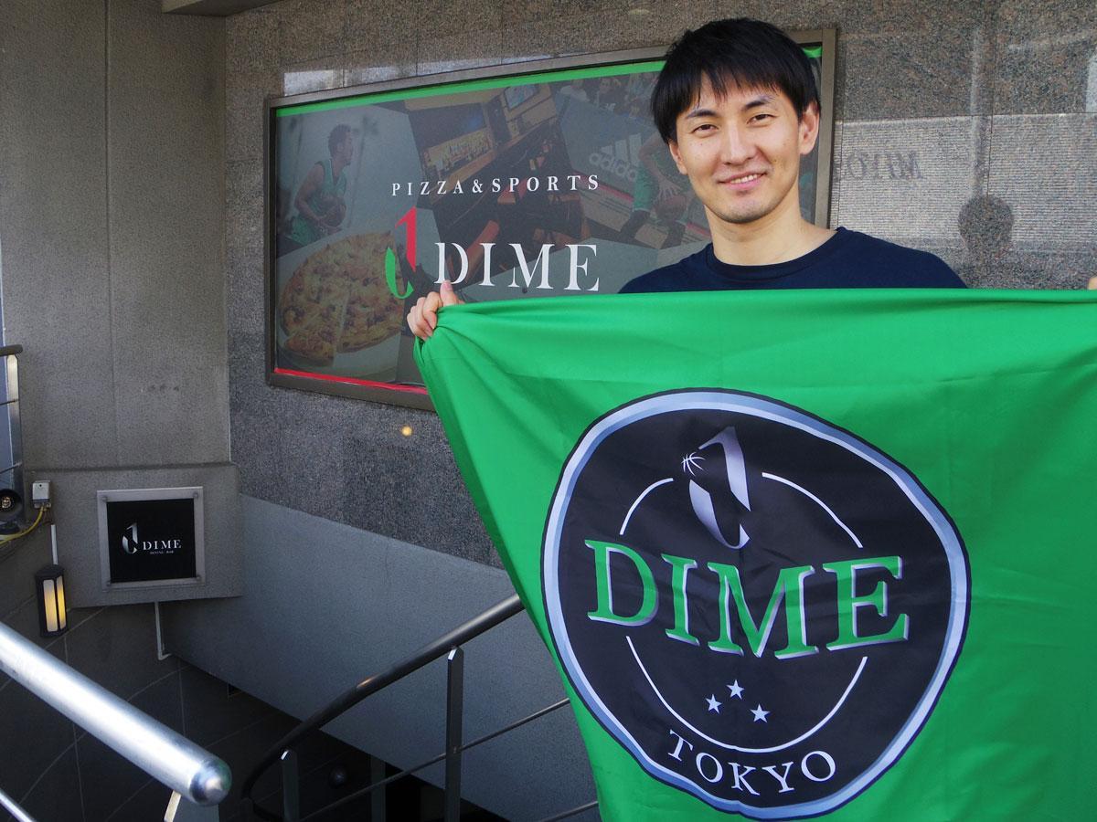 渋谷のスポーツバー「DIME」前でチームフラッグを掲げるオーナー兼選手の岡田優介さん