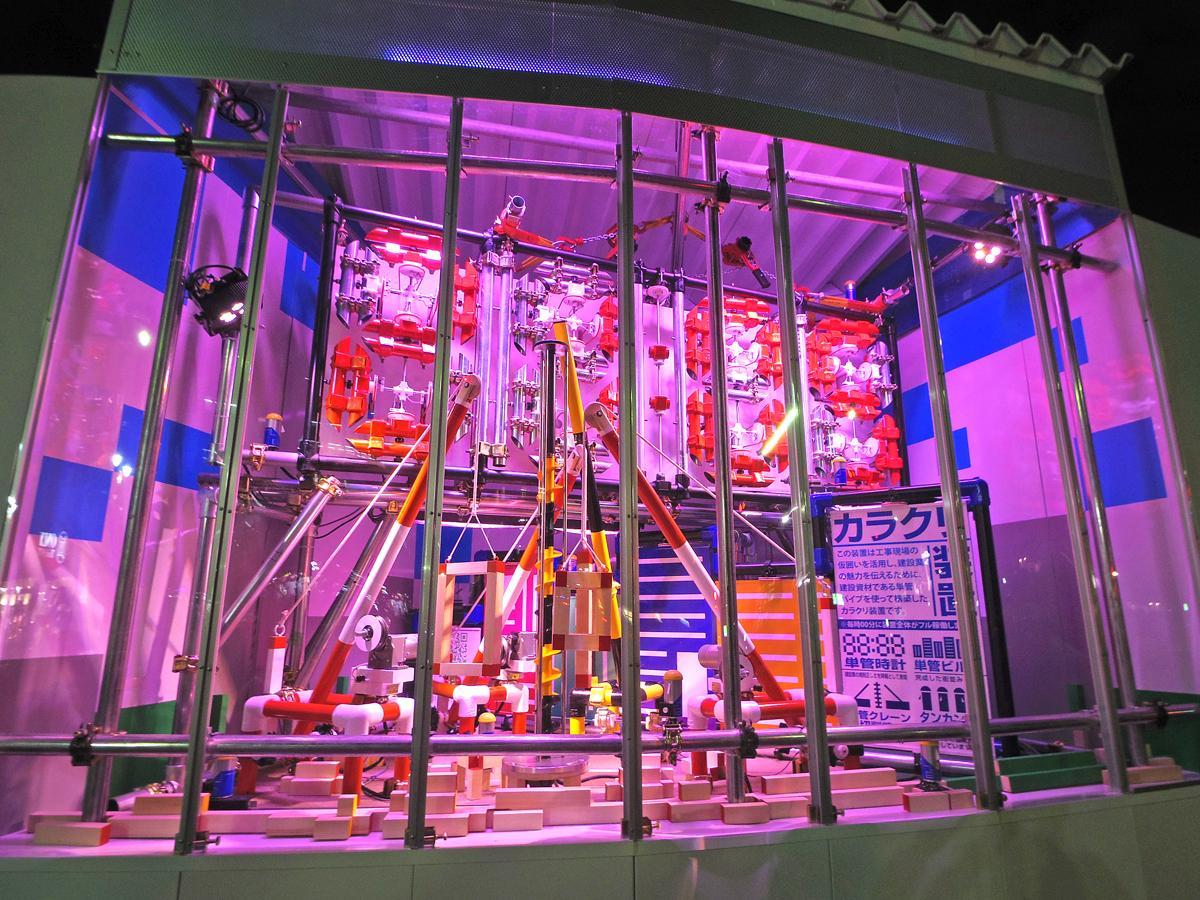 上部にはデジタル表示の時計、下部の装置では単管やパイプを使いクレーンなどの重機やビル群を模した「建設現場」を表現