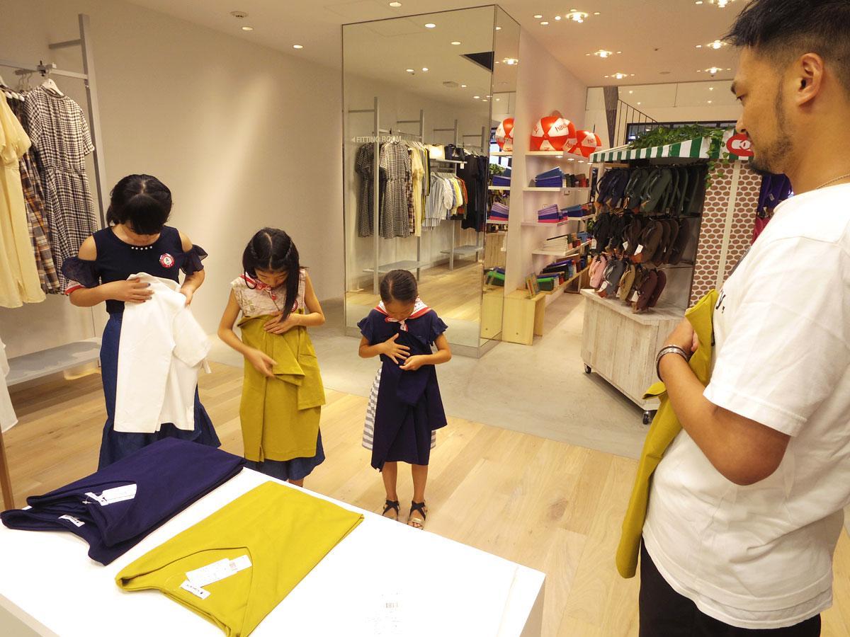 スタッフ指導の下、Tシャツを畳む練習をする参加児童たち
