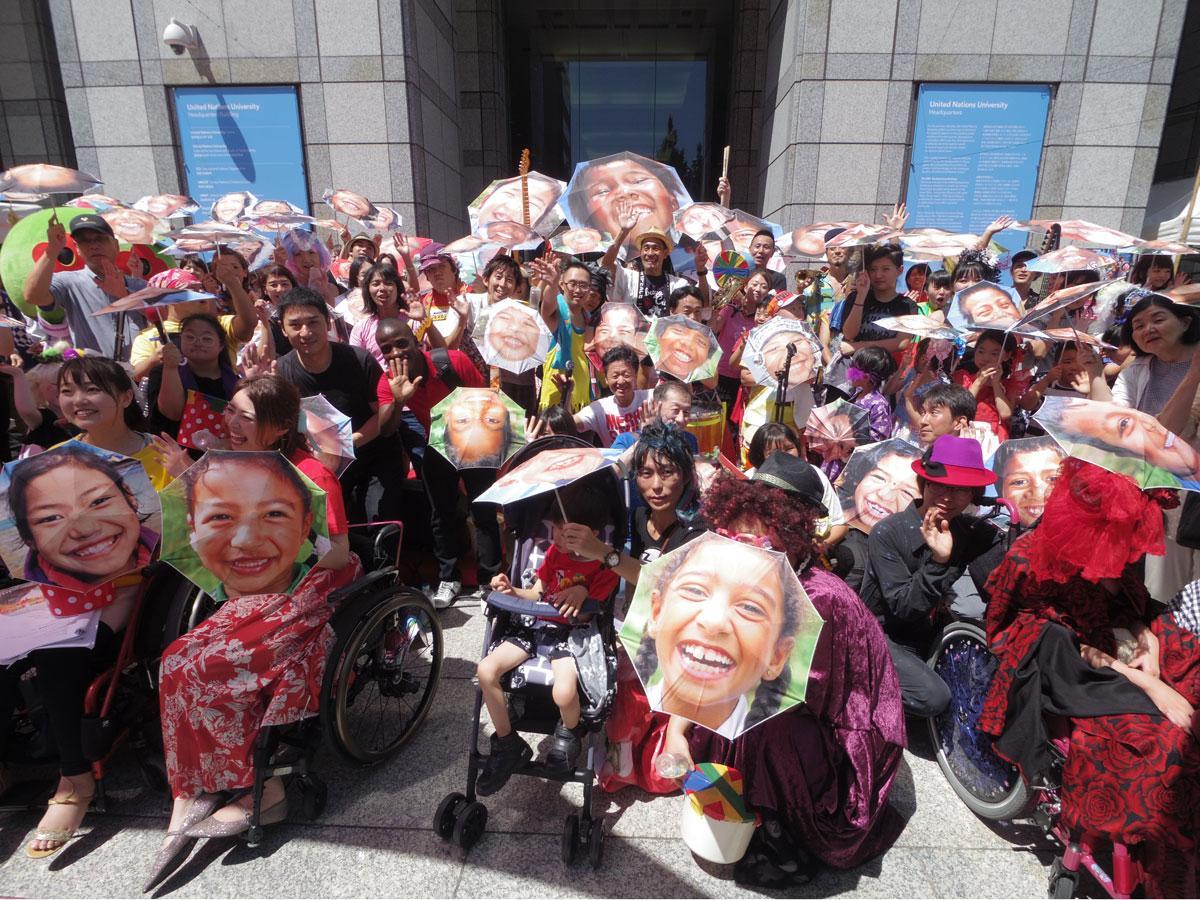 アートディレクターの水谷孝次さんが展開する子どもの笑顔をプリントした傘を開くアートパフォーマンスも行われた