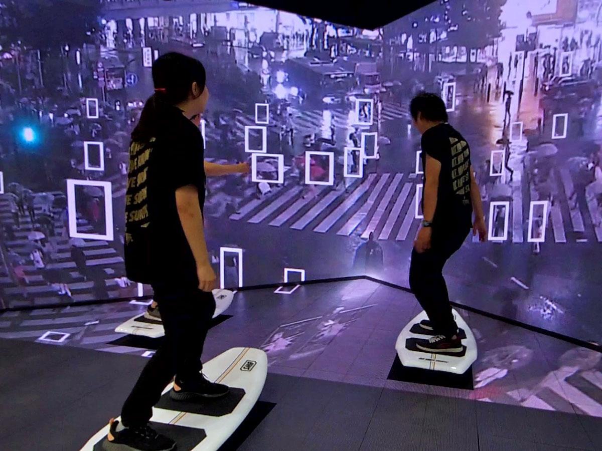 スクランブル交差点を渡る人の量などを解析し作るデジタルの波と連動してサーフボード型のデバイスが動く