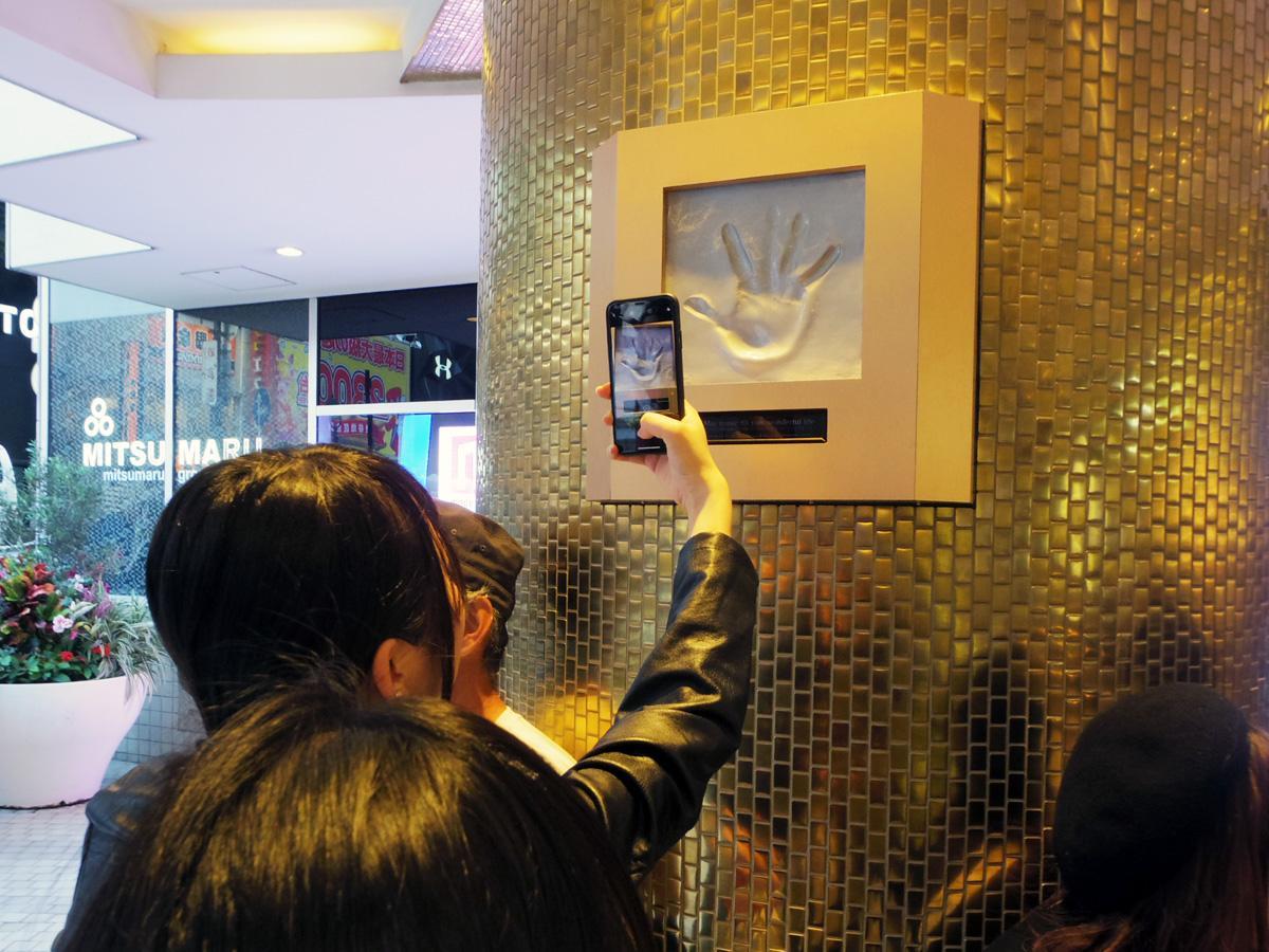 109エントランスに常設された安室さんの手形モニュメント。写真を撮る人の姿も