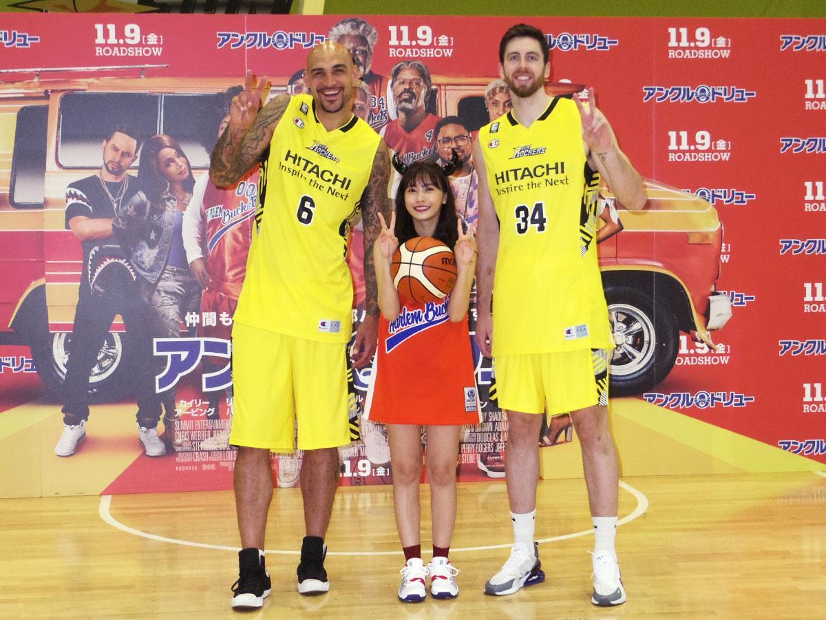身長2メートルを超すロバート・サクレ選手(左)とライアン・ケリー選手(右)に挟まれた佐野ひなこさん