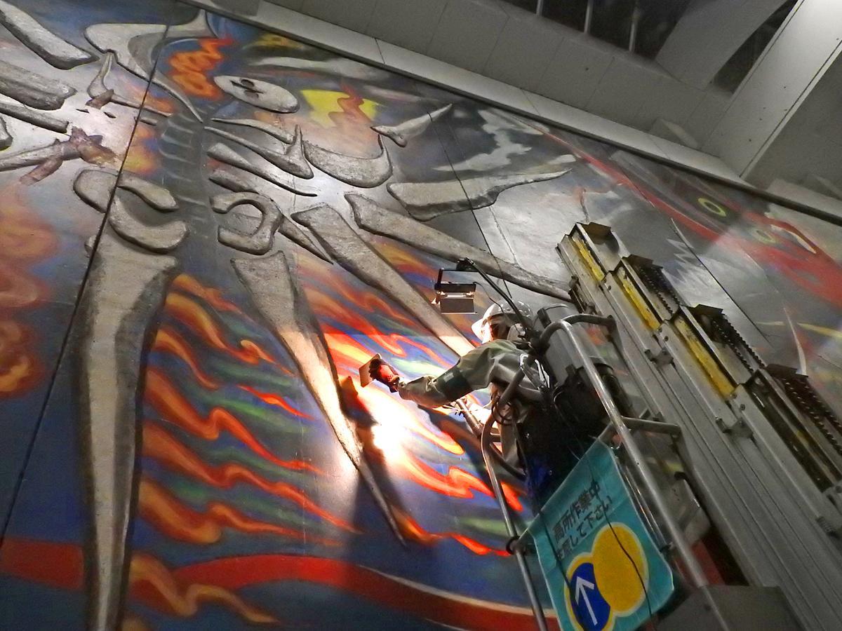 リフターに乗り、壁画に付着した「ホコリ」を取り除くボランティア