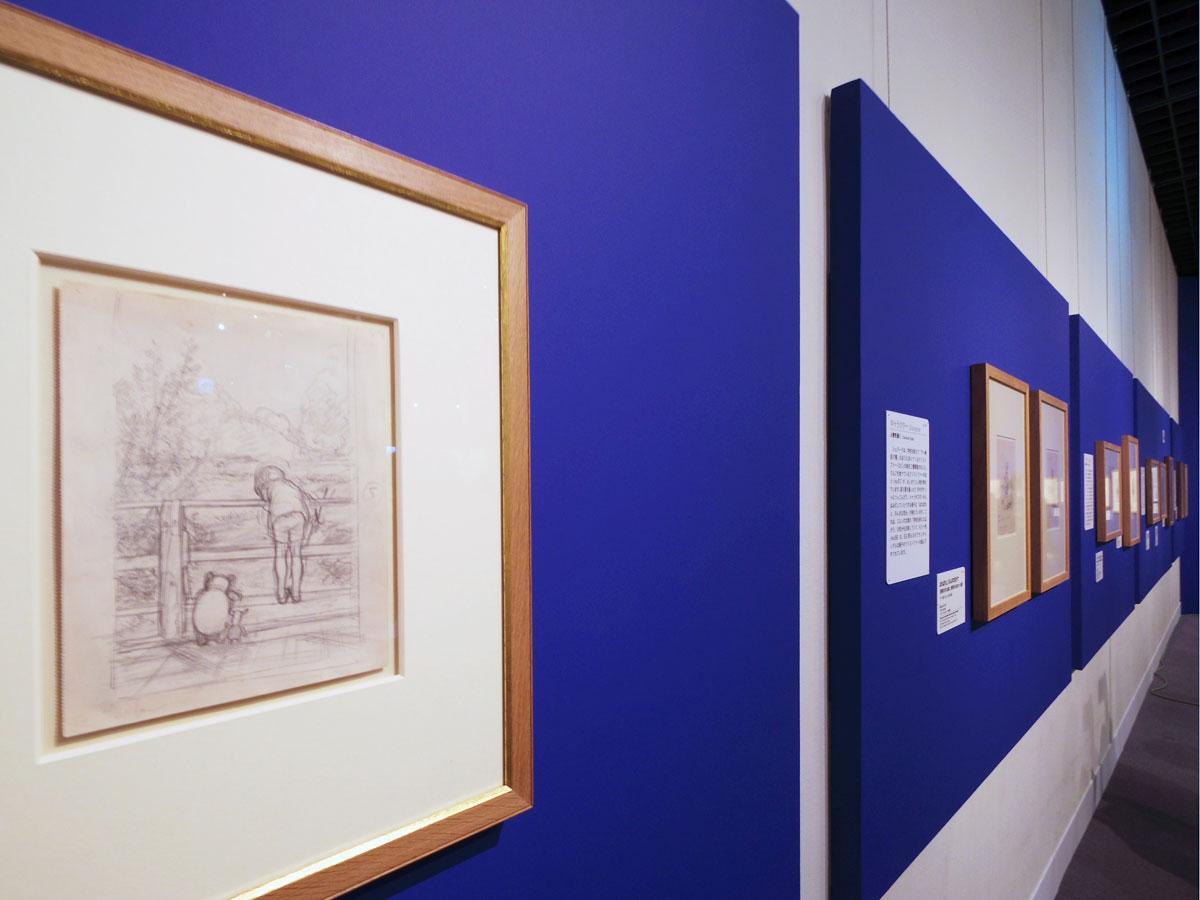 クリストファー・ロビン、プー、コブタが川を眺めているシーン(左)などの原画が並ぶ場内