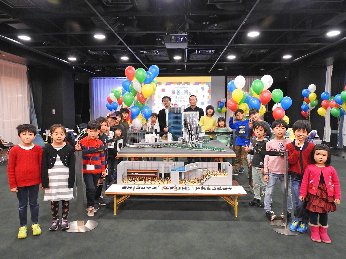レゴブロックで制作したジオラマを囲み、後方中央に三井淳平さん(左)、長谷部健区長(右)、周囲にワークショップを参加した子どもたち
