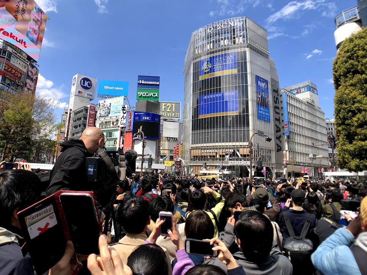 駅前のビジョンに速報が流れた瞬間、多くの人がカメラを向けた