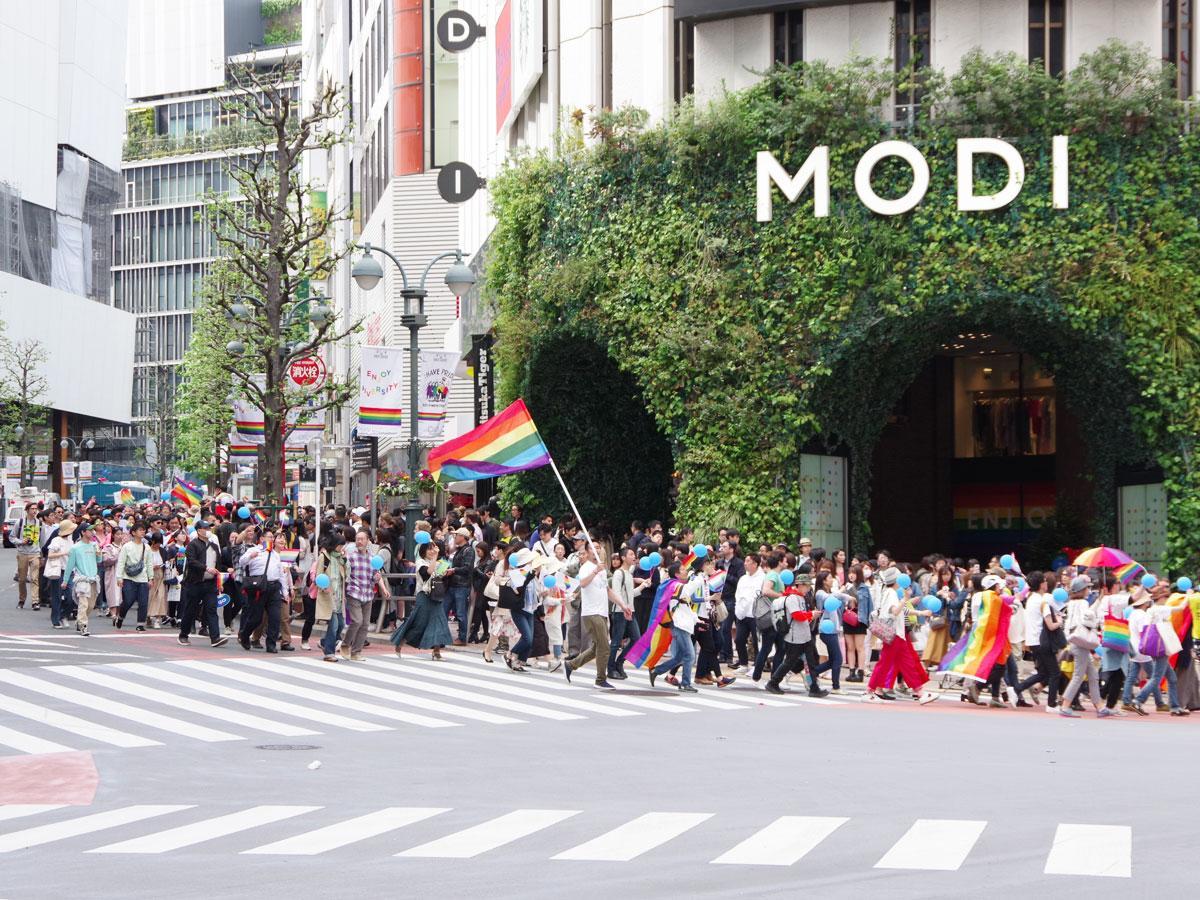 虹色の旗を持った人やカラフルなアイテムを身に付けた約1万人の人たちが街中をパレードした