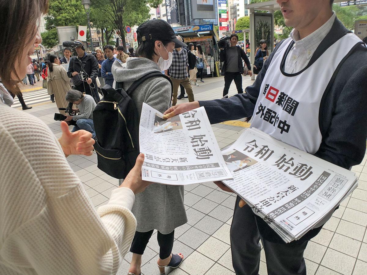 新天皇即位を受け渋谷駅周辺で配られた号外を受け取る人たちの様子
