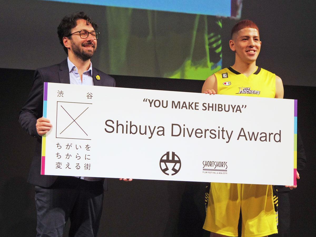 (左から)「Shibuya Diversity Award」を受賞したヴィト・パルミエリ監督とプレゼンターを務めたサンロッカーズ渋谷のベンドラメ礼生選手