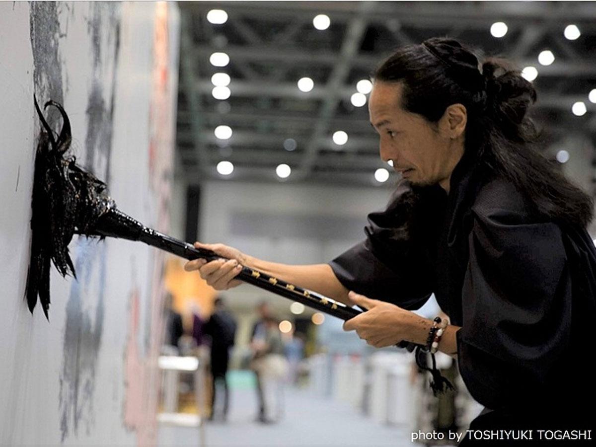 最も多く集まった「一文字」を書道パフォーマンスする墨筆士・小林龍人さん