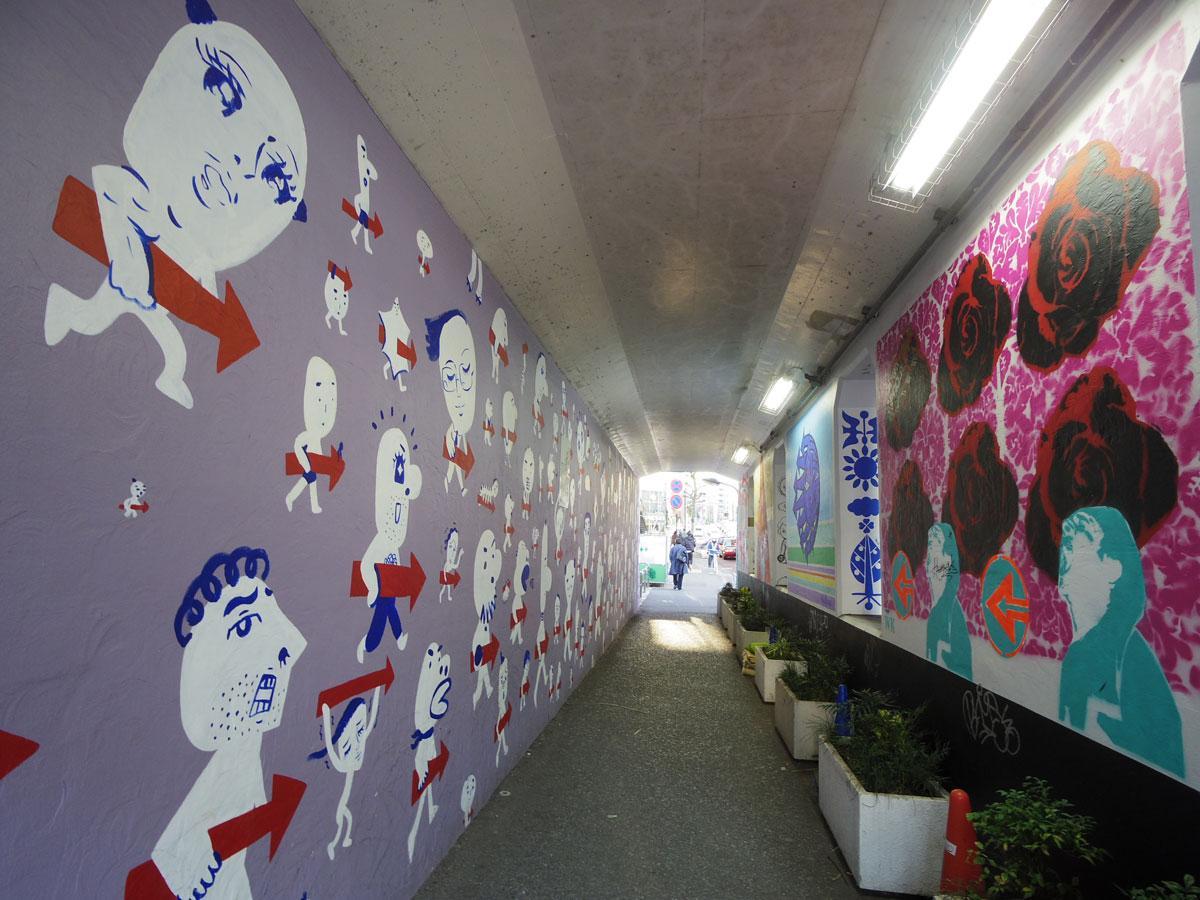 災害時に帰宅困難者を一時退避場所に誘導する「矢印サイン」。左壁面がしりあがり寿さんの作品、右手前の壁面は小町渉さんの作品