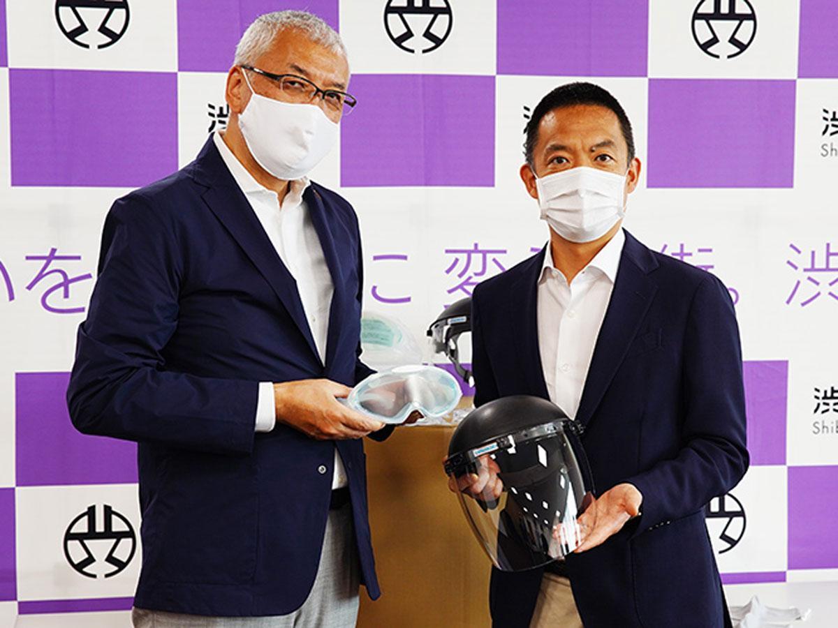 マスクやフェースシールドなどを受け取る長谷部健渋谷区長(右)