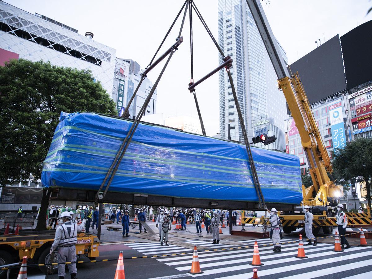 クレーンでつり下げられ大型トレーラーの荷台に載せられる青ガエル(写真提供=渋谷区・大館市)