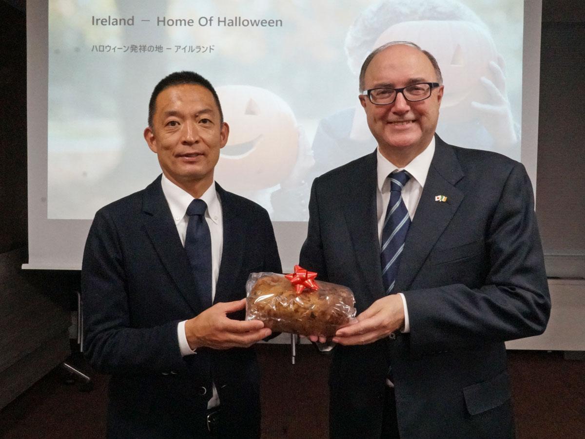 長谷部健渋谷区長(左)にフルーツケーキ「バーンブラック」を手渡したポール・カヴァナ駐日アイルランド大使