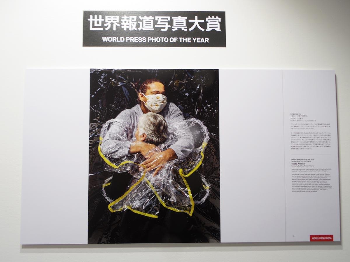 「世界報道写真大賞」に選ばれた透明のカーテン越しに抱擁をする女性2人をとらえた1枚