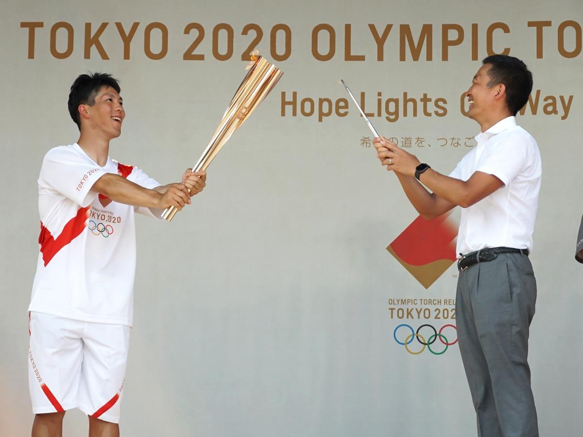 渋谷区「第1走者」の原大智さん(左)のトーチに長谷部健渋谷区長(右)が点火し渋谷区の「聖火リレー」が始まった