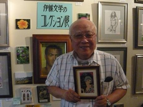 絵葉書の額を持つ伊藤さん。現在はアメリカの古着を収集しており、下北沢で買い物することも多いという