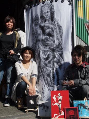 左から岡野さん、若松さん、山下さん。絵はヘッドフォンをするマリア像。「下北沢は音楽の街なので、ここに住むお母さんは胎教にも音楽を使いそうだと思った」(山下さん)