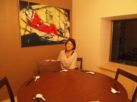 2階に展示されている絵画を前に笑顔の張本里華さん。「日本もNYのように、お店にたくさん絵画を置いて街がアートであふれたらすてきだと思う」。