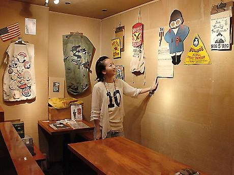 壁一面に作品を展示。バーカウンターでは、缶バッジなどの物販も行う