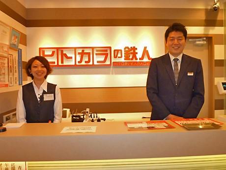 「ヒトカラの鉄人」の受付に立つ、店長の大江さん(右)とアルバイトの女性