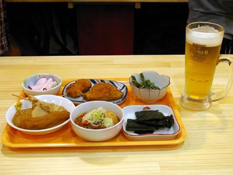左からカブの浅漬け、松江おでん、玉子入り煮込み、串揚げ、アジフライ、板わかめ、いんげんのゴマあえ、中ジョッキ。中ジョッキと「玉子入り煮込み」は200円、そのほかは100円