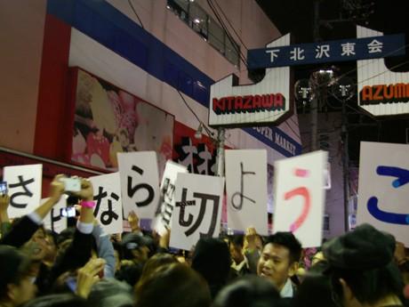 6号踏み切りに集まった人たちが掲げた「さよなら踏み切り ようこそシモチカ!」のプレート