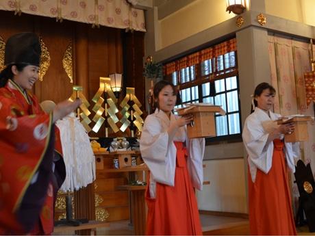 神主の手塚さん(写真左)から、三方(さんぽう)の持ち運び方を教わる参加者