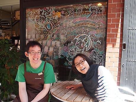 今月のイラスト「梅雨」の前に座る谷川隆次さん(左)とおおがきなこさん(右)