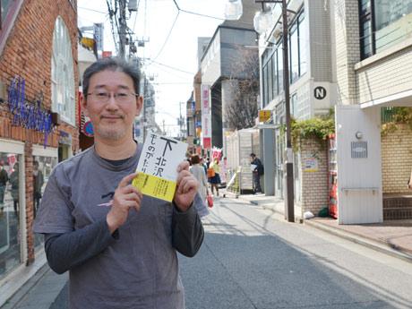 「下北沢ものがたり」を手に、下北沢の街に立つ企画者の播磨さん