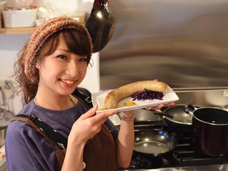 「オリジナルソーセージ」(750円)を提供するホール担当の成松愛さん。成松さんはキッチン担当のJumboさんが以前勤務していたタイ料理店の常連で「Jumboさんの料理のファン」だったそう