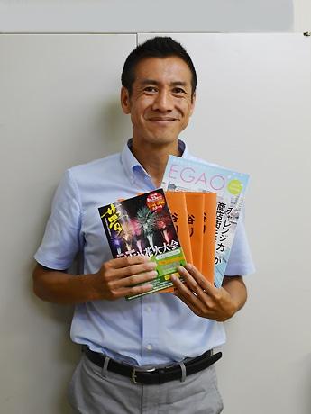 さまざまな街のガイドブックを手にする廣田さん
