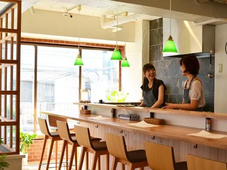 カウンター内でおしゃべりをしながら料理を作る松田さん(左)と相原さん(右)。「お代わりくださいと言われるとうれしい」と笑顔で話す