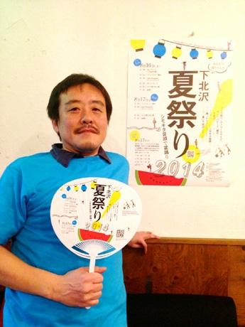 「下北沢夏祭り2014」のポスターの前で同祭のうちわと一緒に映る実行委員長の岩本健一さん