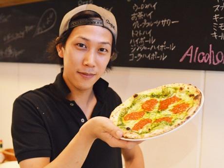 店長の世木さんと、焼きたての「イタリアンバジル」(500円)。土曜は3時間で4~50枚のピザが出ることもあるという