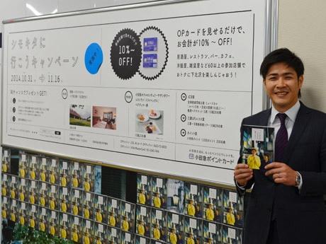 下北沢駅構内で冊子ラックの横に立つ木谷さん