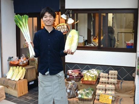 契約農家から届いた大根とネギを持って店頭に立つ、店長の武中俊樹さん
