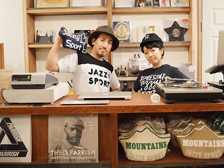 """「JS """"ロゴ"""" クッション」(4,500円)を手に持つIZMさん(左)と、「JS ウール ベースボールキャップ」(4,800円)をかぶるスタッフPericoさん"""