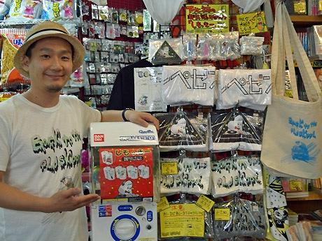 画像キャプション:担当者の中野雄介さん。ガチャガチャの横にはしもっきーグッズが並ぶ