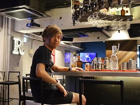 店内バーカウンターに座る、村岡俊介社長
